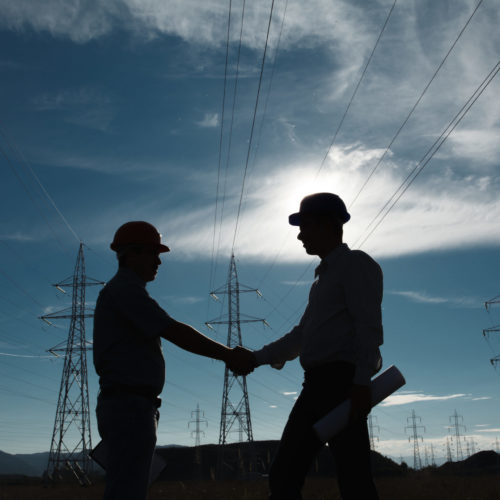 Two men shaking hands under electrical power lines.