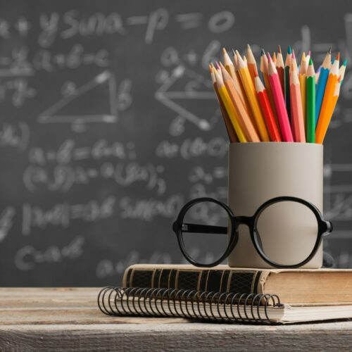 Colored pencils and glasses sit on a book and notebook in front of a blackboard.