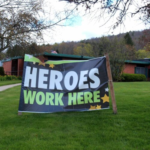 Banner outside of an American nursing home saying heroes work here.