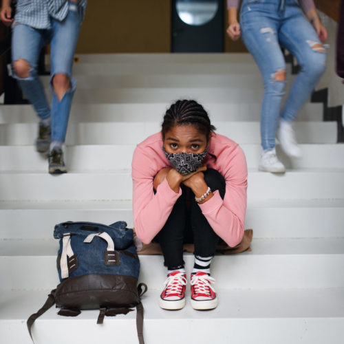 A young student with a face mask sits on stairs as other students move around her.