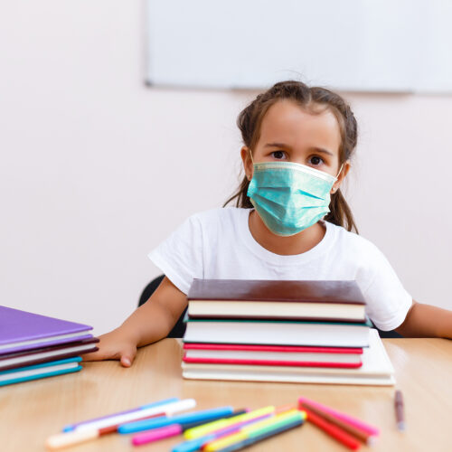 child with mask and books